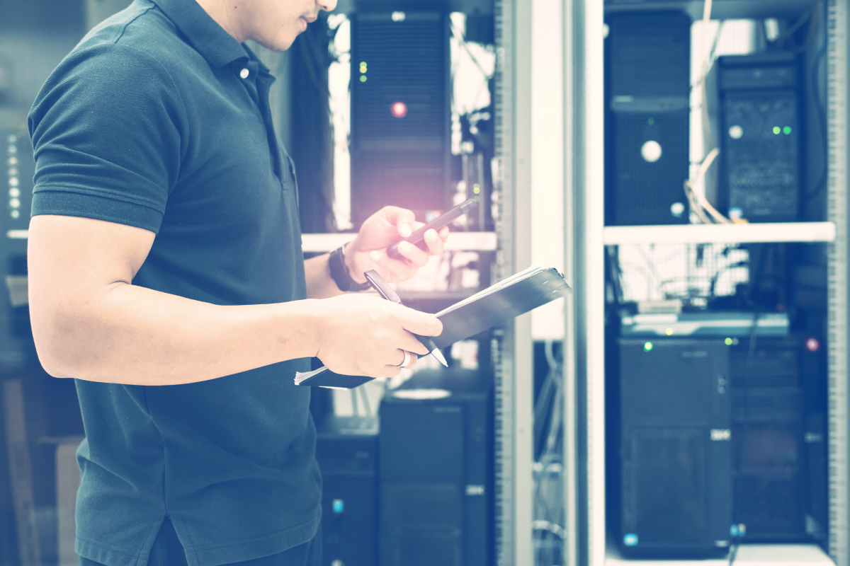 IT Technician Holding Cell Phone and Clipboard Standing in Data Center