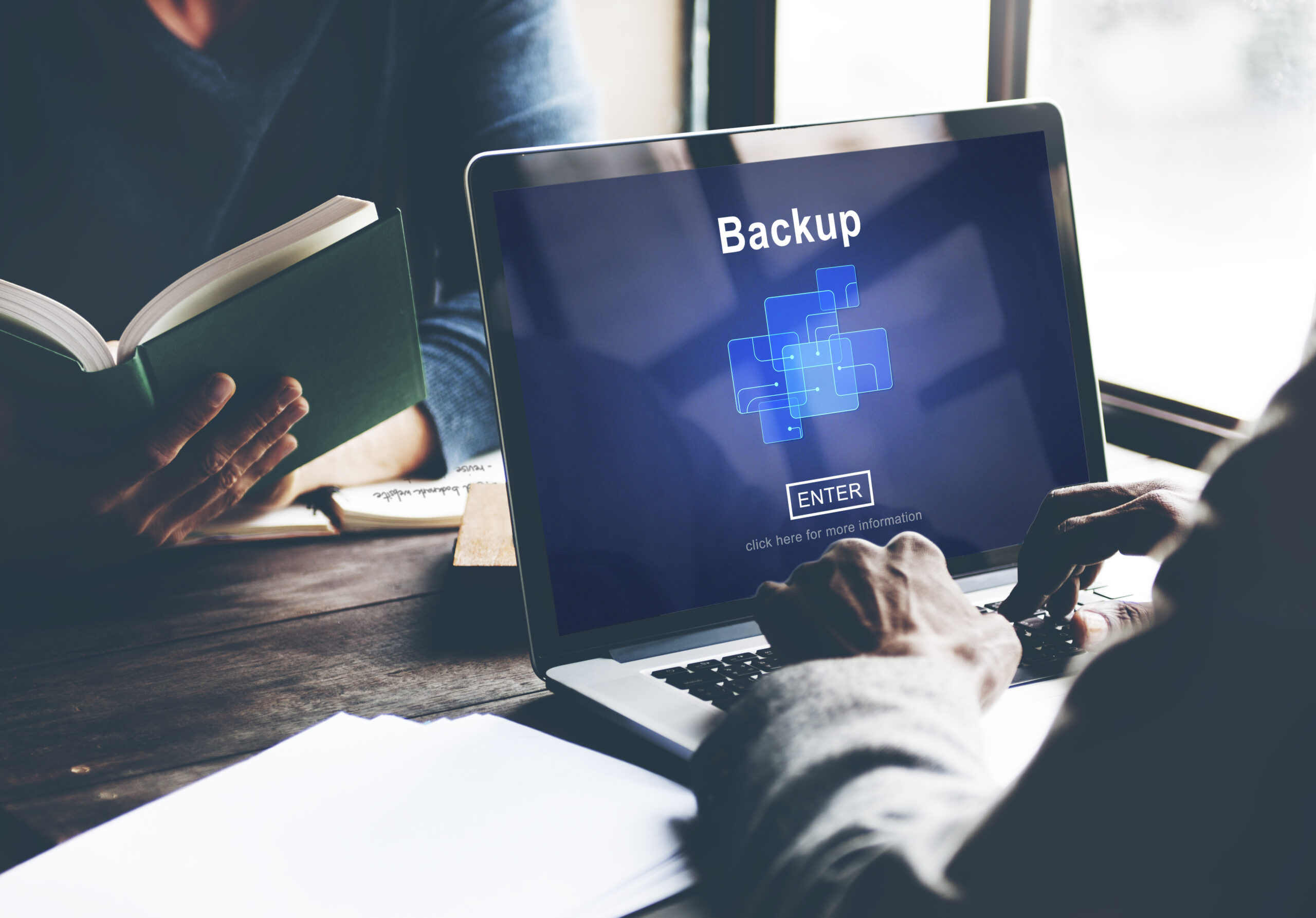 Person Sitting at Laptop Computer with Backup Process on Screen