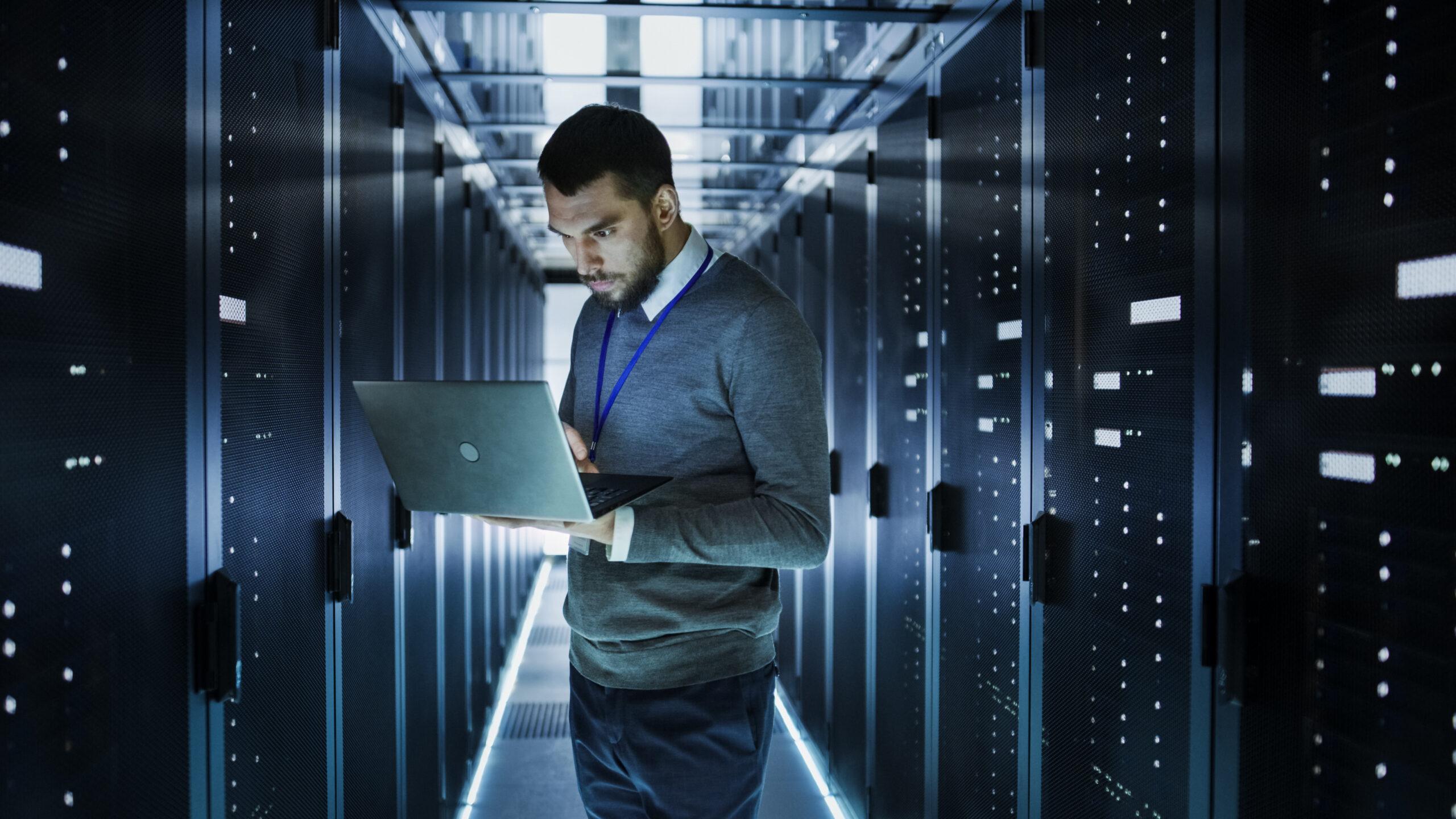 Man Holding Laptop in Data Center