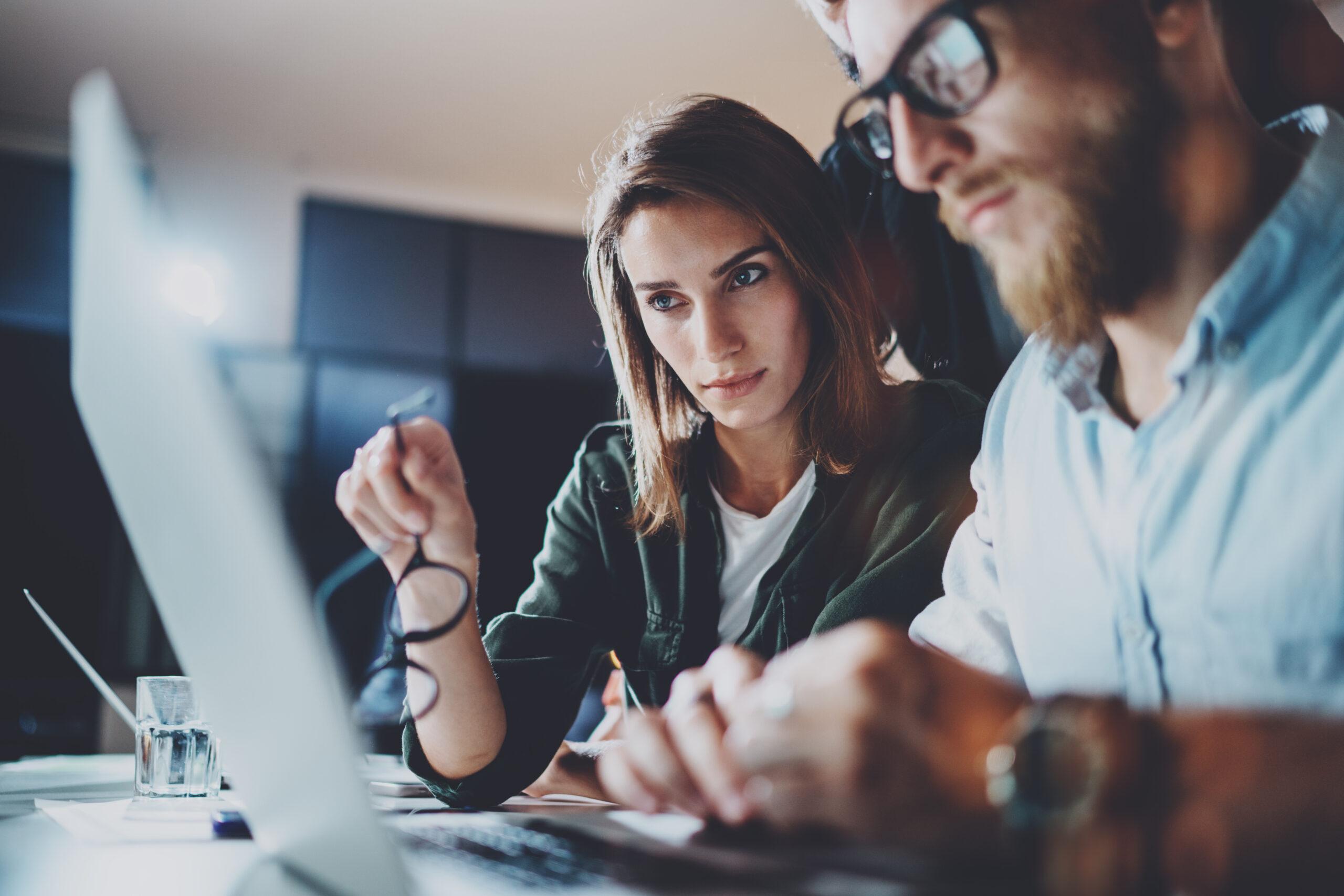 Man and Woman Sitting at Desk, Looking at Laptop Computer