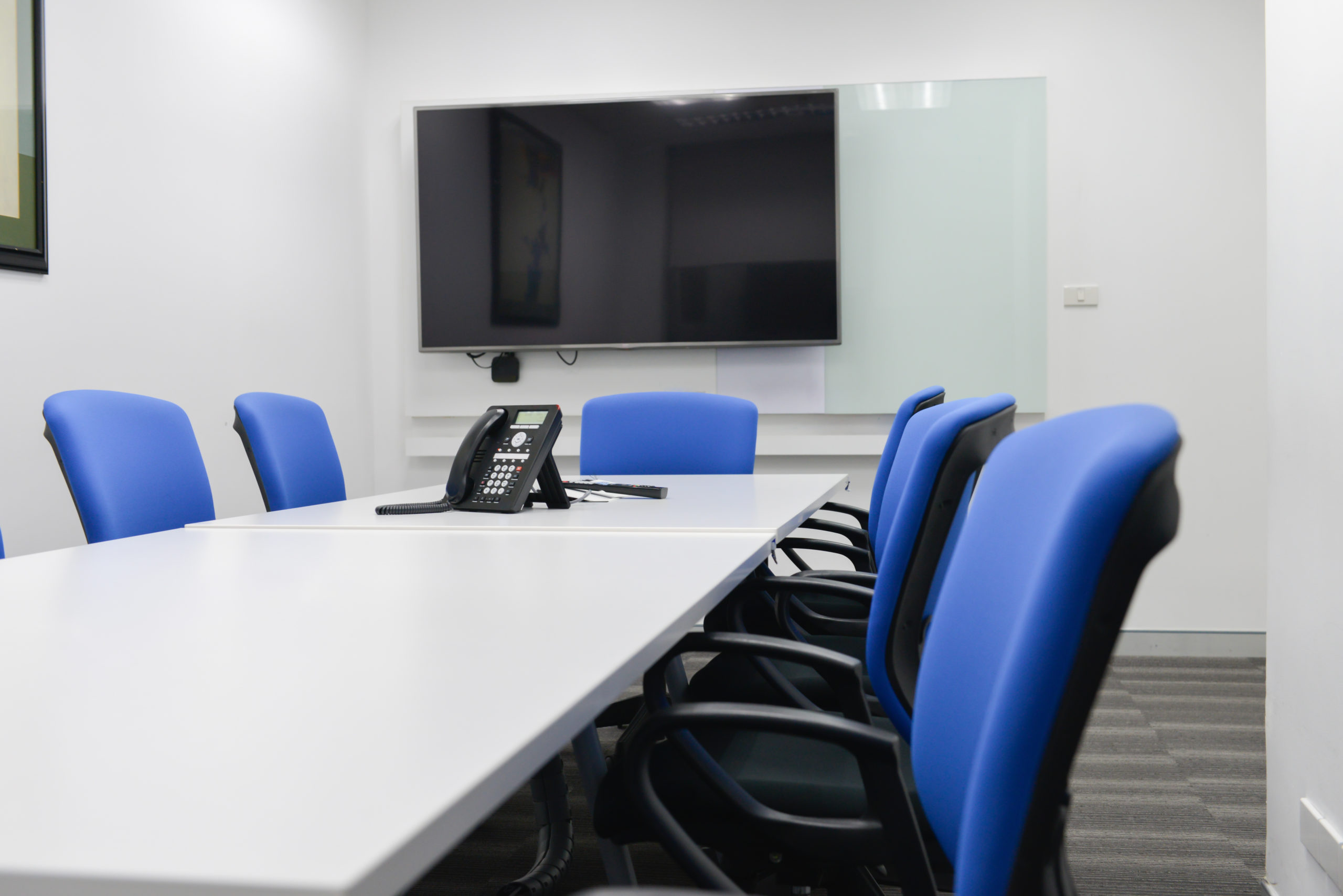 White Conference Room Desk with Blue Chairs, VoIP Phone on Desk and Screen in Background