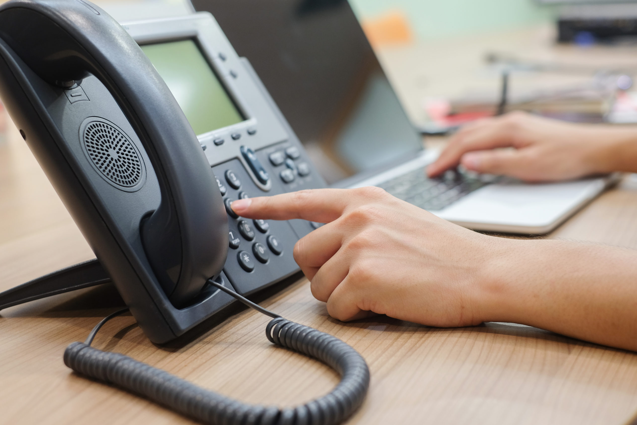 Close Up of Hands Dialing VoIP Phone